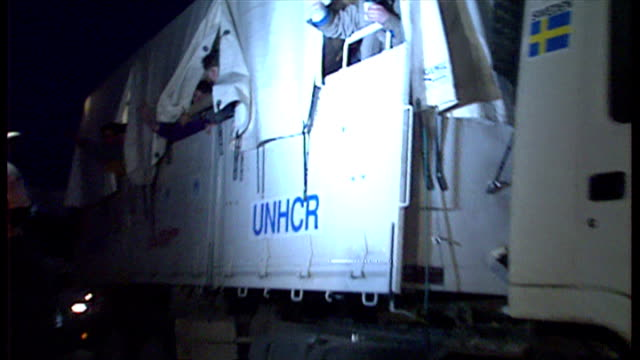 Exterior shots at dusk of a convoy of UNHCR lorries carrying refugees across into Bosnian Muslim territory in Srebrenica on April 13 1993 in...