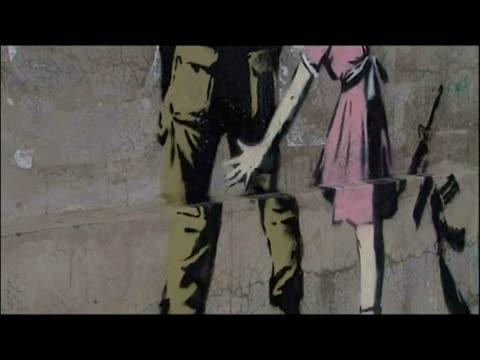 Exterior shots Banksy graffiti paintings murals on West Bank walls General shots men at work putting up Banksy art on wall