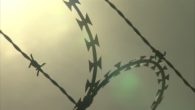 Exterior shots barbed wire fencing running along edge of Calais port with sun setting in background on August 02 2016 in Calais France