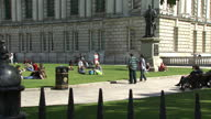 Exterior shots Belfast City Hall on a sunny day people sitting on grass in the sunshine