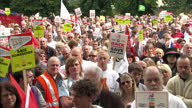 Exterior shots Bombardier staff protesters gathered together marching through street holding placards banners Bombardier Staff in Protest March in...