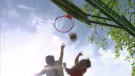 Exterior shots boys teenagers playing basketball in park Exterior shots basketball hoop against blue sky anonymous jumps up and shoots hoop on May 25...