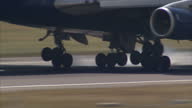 Exterior shots British Airways Boeing 747 passenger plane landing at Heathrow airport with closeup shot of plane wheels touching down on runway on...
