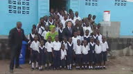 Exterior shots British Prime Minister David Cameron Liberian President Ellen Johnson pose for family photo with pupils from Anna Whisnant Elementary...