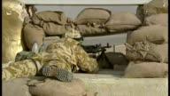 Exterior shots British soldier manning machine gun post under defaced statue and portrait of Saddam Hussein at the start of the 2003 Invasion of Iraq...
