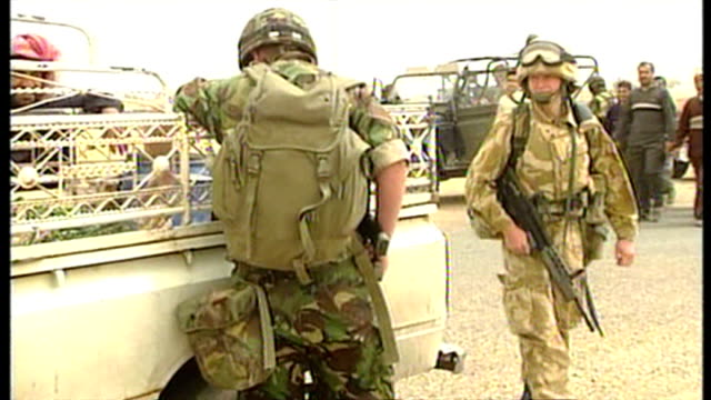 Exterior shots British soldiers at road checkpoint in Southern Iraq stopping and searching vehicles driven by Iraqi civilians at the start of the...