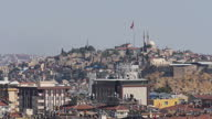 Exterior shots buildings on Gaziantep city skyline with mosque on hilltop large Turkish flag flying over city on October 10 2015 in Gaziantep Turkey