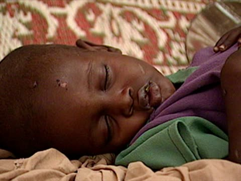 Exterior shots child sleeping while flies crawl over face on April 04 2000 in South Eastern Ethiopia