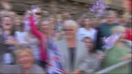 Exterior shots crowds of well wishers stood behind barricades waving Union flags as they await the arrival of Zara Phillips Mike Tindall Crowds Wait...