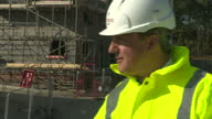 Exterior shots David Cameron British Prime Minister on visit to new homes construction site talking to construction workers and wearing a high...