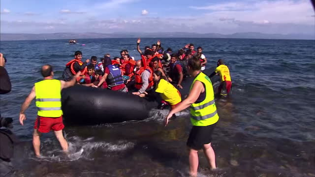 Exterior shots dinghy packed with migrants arrives on beach and volunteers help carry children from the boat to the shore on October 15 2015 in...