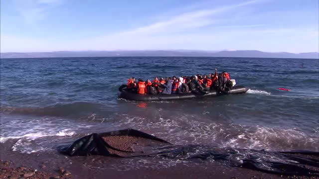 Exterior shots dinghy packed with migrants arrives on beach Migrants wearing orange life jackets wave to people on the shore and help each other get...