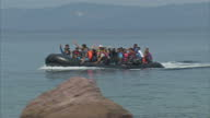 Exterior shots dinghy packed with Migrants arrives on Lesbos beach with migrants waving and cheering Volunteers help the migrants out of boat and...
