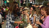 exterior shots Duchess of Cambridge speaks to supporters behind barrier and accepting gifts