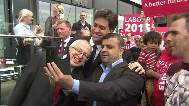 Exterior shots Ed Miliband Labour Party leader meeting party activists students taking selfie photo with supporters outside University Campus Suffolk...