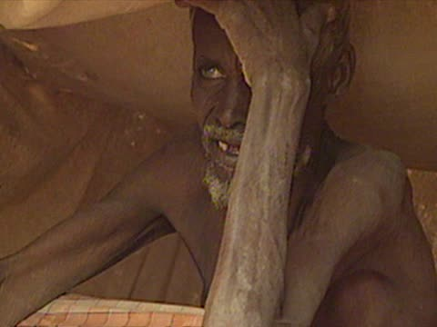 Exterior shots elderly man sitting in tent young emaciated boy being given water from a cannister on April 04 2000 in South Eastern Ethiopia