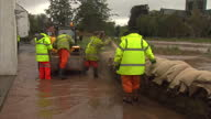 Exterior shots emergency workers laying sandbags by building as heavy flood waters surround the area Exterior shots rising flood waters flowing under...
