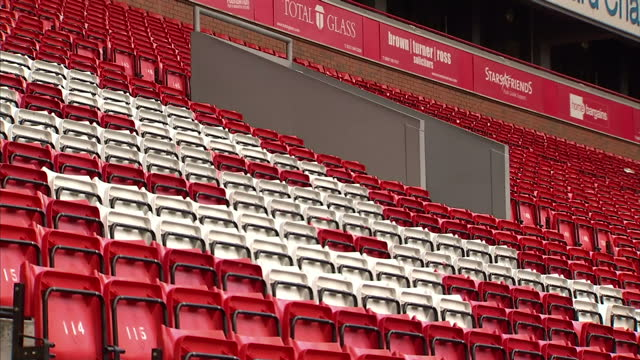 Exterior shots empty Anfield football stadium seats with closeup of club crest on top of stand and view across pitch on in Liverpool England