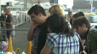 exterior shots family and friends of MH17 victims crying and hugging each other around flower memorial outside airport