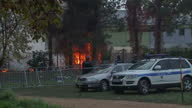 Exterior shots fire raging at a migrant camp in Slovenia with police officers at the scene and migrants on opposite side of fencing Fire emergency...