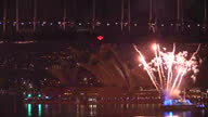 Exterior shots fireworks exploding from Royal Australian Navy warship under Sydney Harbour Bridge with the Opera House in the background The...