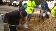 Exterior shots flood hit residents filling sandbags to build flood defences on in Somerset United Kingdom
