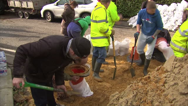 Exterior shots flood hit residents filling sandbags to build flood defences on in Somerset United Kingdom