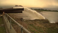 Exterior shots flood water being pumped through large pipes into reservoir at sunset on February 13 2014 in Somerset United Kingdom