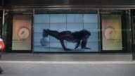 Exterior shots focus on a Plasma Screen video display showing a woman exercising in the window of Niketown on 57th Street in New York NY