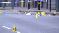 Exterior shots forensic officers in white overalls on the street placing numbered evidence markers on the road Three people have died after being hit...