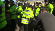 Exterior shots fracking protesters stand off with police man being wrestled to the ground arrested on March 11 2014 in Eccles England