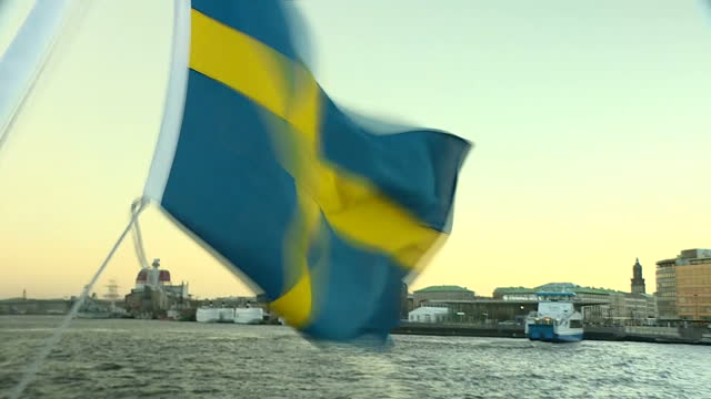 Exterior shots from a sightseeing boat travelling along the Gota Alv River in Gothenburg including views with the Swedish flag on the stern of the...