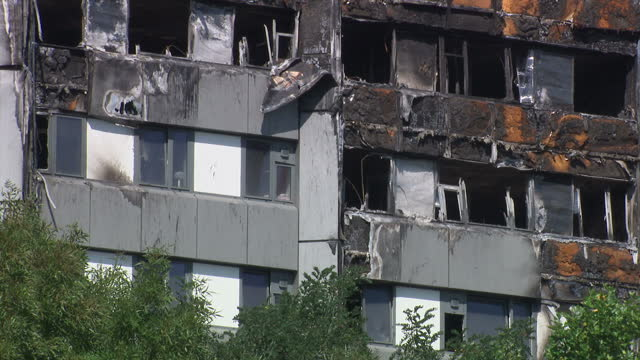 Exterior shots Grenfell Towers with the shell of the building burnt out wreckage of the building with men in white overall suits and protective face...