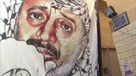 exterior shots hanging banner with face of Yasser arafat pan to Street sign in West Bank displaying distance to Jerusalem Yasser Arafat Art and West...