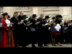 exterior shots HRH Prince Charles Camilla Duchess of Cornwall stand singing from hymn sheets in front of cenotaph