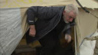 Exterior shots Jeremy Corbyn Labour Leader on visit to migrant camp in Calais Talks with people and goes into small tent to change his shoes on...