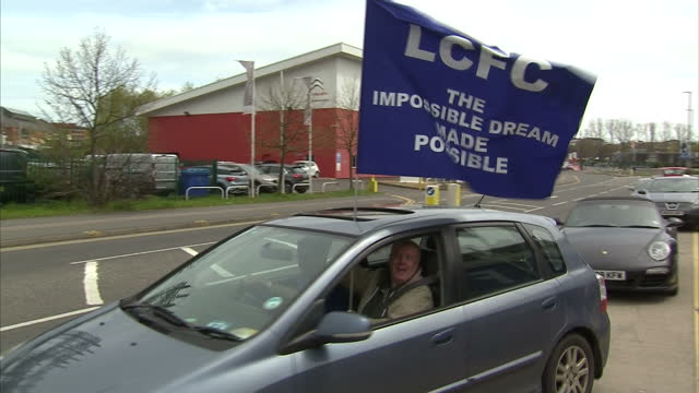 Exterior shots Leicester City fan standing out of car sunroof holding large Leicester City flag reading 'LCFC The Impossible Dream Made Possible' and...
