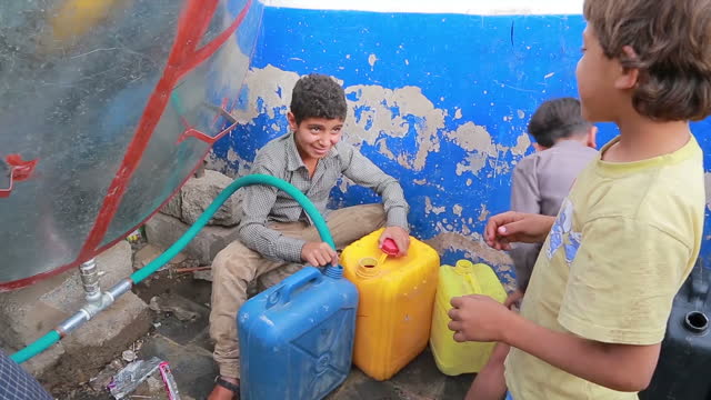 Exterior shots life around Sana'a traffic children filling up containers with water man filling car with petrol on June 15 2015 in Sana'a Yemen