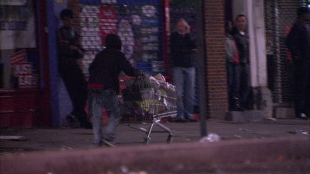 Exterior shots looter pushes shopping trolley down the street London Riots Looting on July 07 2011 in London