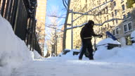 Exterior shots man trying to clear thick snow and ice from pavement with snow shovel after Winter Storm Jonas hit the US East Coast on January 23...