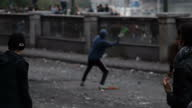 Exterior shots masked protesters throwing stones at line of police Exterior shots plumes of tear gas smoke surrounds protesters Protesters Throw...