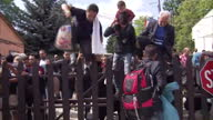 Exterior shots migrants refugees asylum seekers getting off bus and climbing over fence in Bicske on September 04 2015 in Bicske Hungary