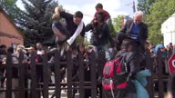 Exterior shots migrants refugees asylum seekers jumping fences leaving escaping Bicske refugee camp on September 04 2015 in Bicske Hungary