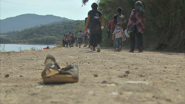 Exterior shots migrants walking down road after arriving on Lesbos beach beginning their long journey to central Europe on September 09 2015 in...