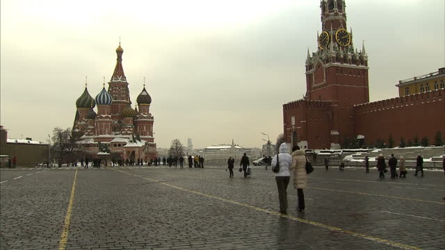 Exterior shots Moscow's red square with Saint Basil's Cathedral and the Spasskaya Tower as tourists walk through the square on January 21 2016 in...