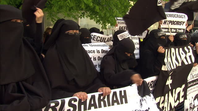 Exterior shots muslim women wearing burkas protesting outside the French embassy holding banners placards such as 'Shariah for France' Exterior shot...