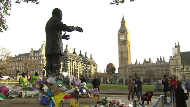 Exterior shots Nelson Mandela statue in Parliament Square with floral tributes at base statue Nelson Mandela Statue In Parliament Square on December...
