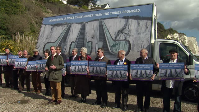 Exterior shots Nigel Farage UKIP leader unveils UKIP Immigration campaign poster in front of the white cliffs of Dover Poster shows three escalators...