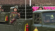 Exterior shots North Korean military vehicles with mounted missile launchers and soldiers sitting on side of vehicles at Workers Party 70th...