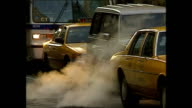 Exterior shots NYC Yellow Taxi Cabs and buses driving along busy streets on November 05 1996 in New York City